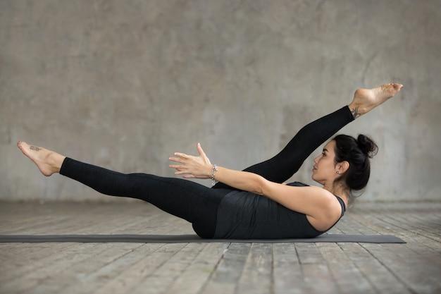 Jonge vrouw die de afwisselende oefening van het beenrek doet