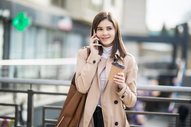Jonge vrouw die de de koffiekop en telefoon lopen van de straatholding