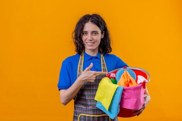 Jonge vrouw die de emmer van de schortholding met het schoonmaken van hulpmiddelen draagt die met vinger ernaar richten glimlachend status over geïsoleerde oranje achtergrond