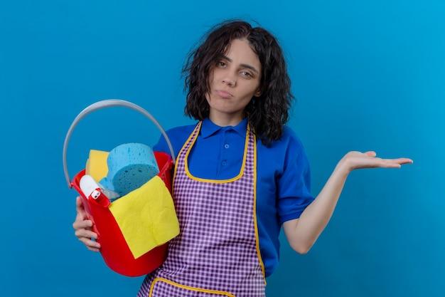 Jonge vrouw die de emmer van de schortholding met het schoonmaken van hulpmiddelen draagt die verward kijken zonder antwoord die zich over blauwe achtergrond bevinden