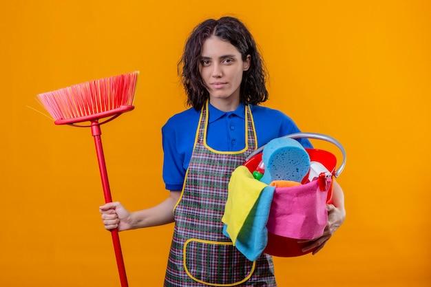 Jonge vrouw die de emmer van de schortholding met het schoonmaken van hulpmiddelen en dweil draagt ?? die camera met ernstige zekere uitdrukking bekijkt die zich over oranje achtergrond bevindt