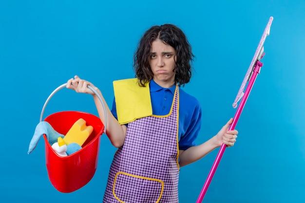 Jonge vrouw die de emmer van de schortholding met het schoonmaken van hulpmiddelen en dweil draagt die overwerkt en moe kijkt die haar wangen blaast die zich over blauwe achtergrond bevinden