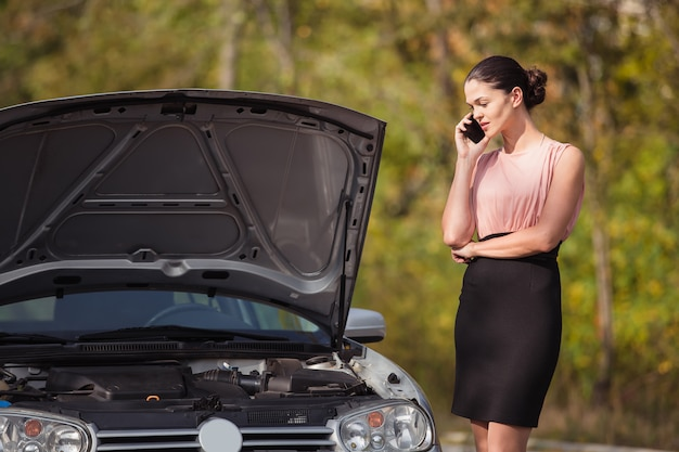 Jonge vrouw die de evacuatiedienst oproepen. haar auto ging kapot op de weg.