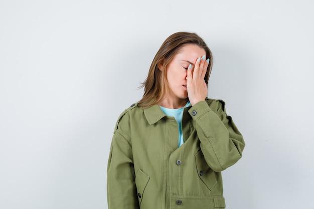 Jonge vrouw die de hand op het gezicht houdt in een groen jasje en er depressief uitziet, vooraanzicht.