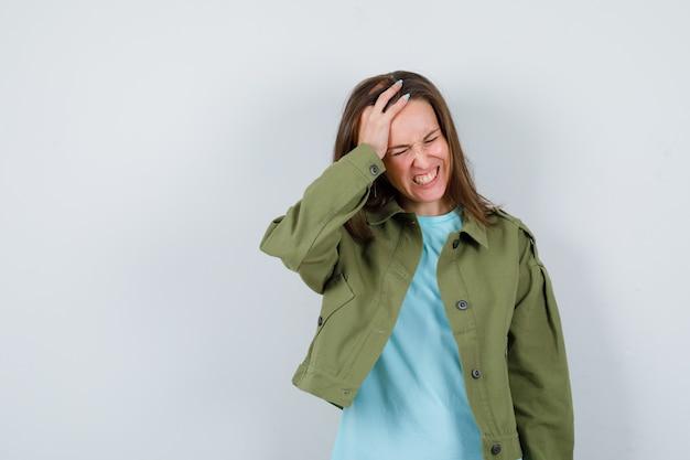 Jonge vrouw die de hand op het hoofd houdt in een t-shirt, een jas en er geïrriteerd uitziet. vooraanzicht.