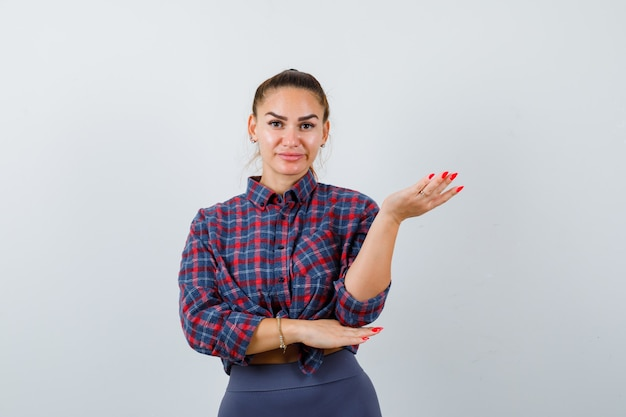 Jonge vrouw die de hand uitrekt in een vragend gebaar in een geruit hemd, een broek en er hulpeloos uitziet, vooraanzicht.