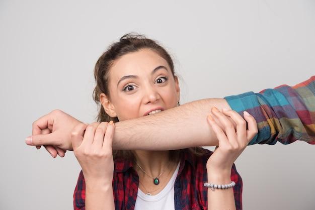 Jonge vrouw die de hand van de man probeert te bijten op een grijze muur.