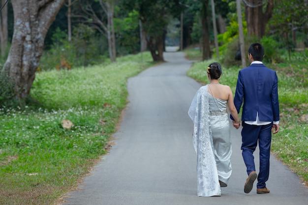 Jonge vrouw die de hand van de man vasthoudt terwijl ze hem leidt in de bloementuin