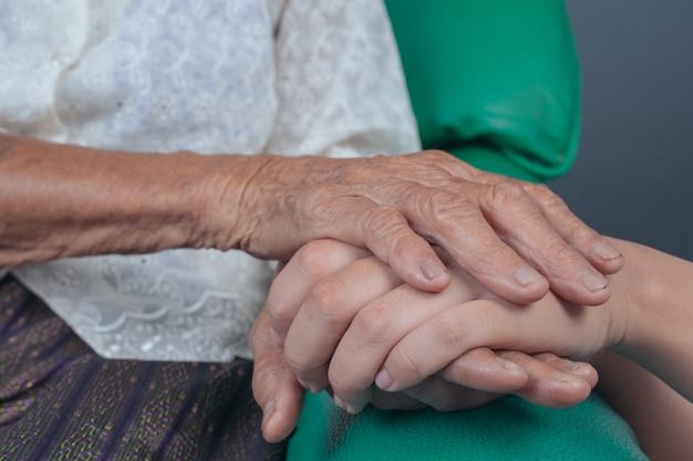 Jonge vrouw die de hand van een bejaarde houdt.