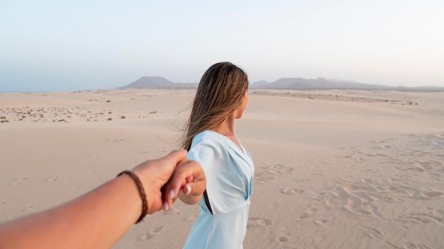 Jonge vrouw die de hand van haar partner vasthoudt tijdens het reizen