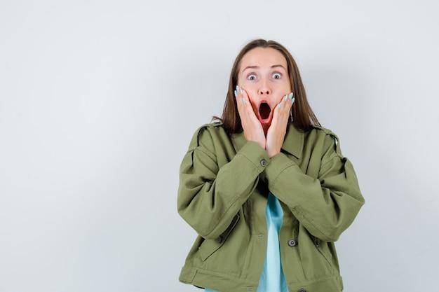 Jonge vrouw die de handen op de wangen houdt in een groen jasje en er geschokt uitziet. vooraanzicht.