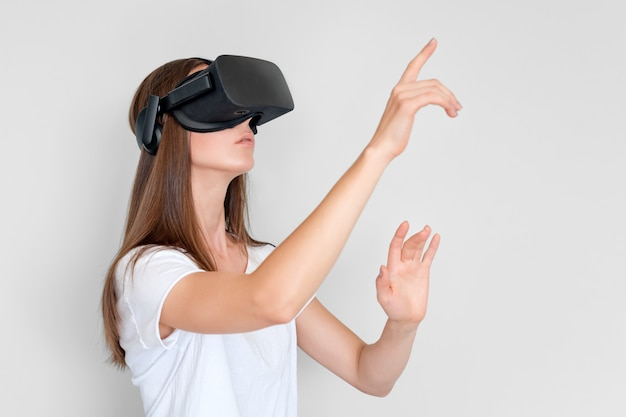 Jonge vrouw die de hoofdtelefoon van virtuele werkelijkheidsbeschermende brillen, vr doos draagt. verbinding, technologie, nieuwe generatie, voortgangsconcept. meisje probeert objecten in virtual reality aan te raken. studio geschoten op grijs