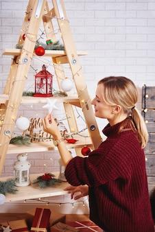 Jonge vrouw die de kerstboom verfraait