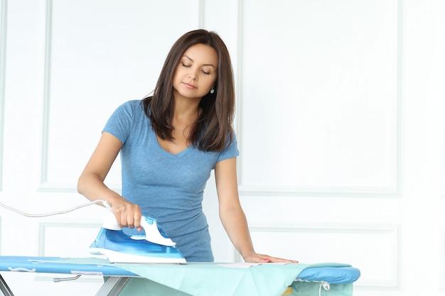 Jonge vrouw die de kleren strijken