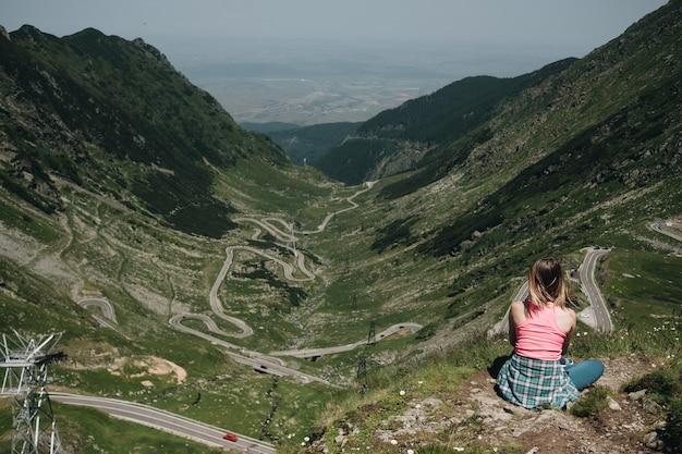 Jonge vrouw die de klippenrand zitten die vanaf de bovenkant de bergweg van transfegerasan bekijken.