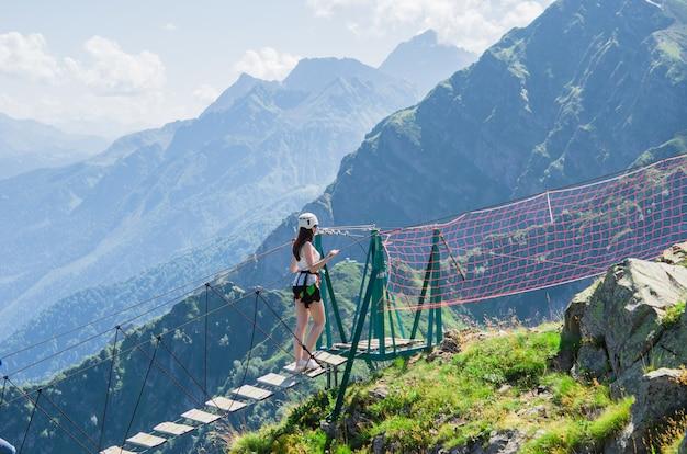 Jonge vrouw die de kloof op de kabelbrug kruist, sotchi, rusland