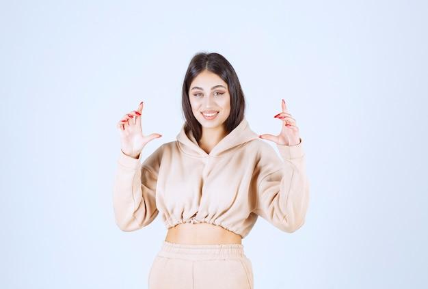 Jonge vrouw die de maatregelen van een voorwerp toont