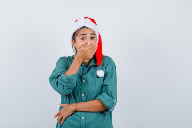Jonge vrouw die de mond bedekt met haar hand, een kerstmuts draagt en er geschokt uitziet. vooraanzicht.