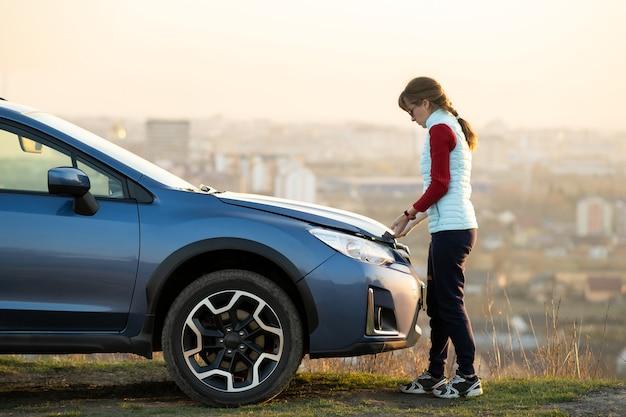 Jonge vrouw die de motorkap opent van een kapotte auto die problemen heeft met haar voertuig. vrouwelijke bestuurder die zich dichtbij auto met opgedoken kap bevindt.