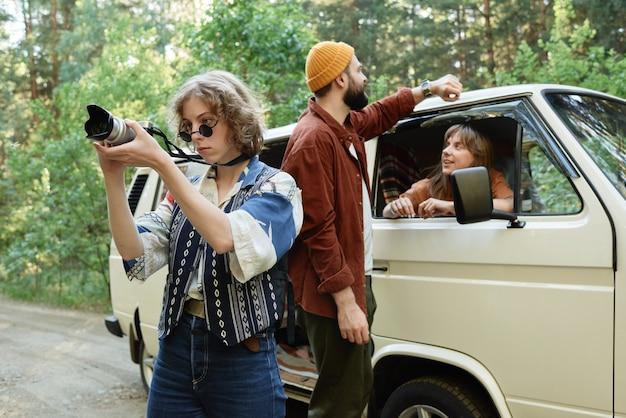 Jonge vrouw die de natuur fotografeert terwijl ze met haar vrienden in de auto reist