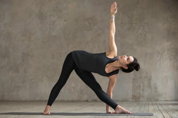 Jonge vrouw die de oefening van utthita doet trikonasana