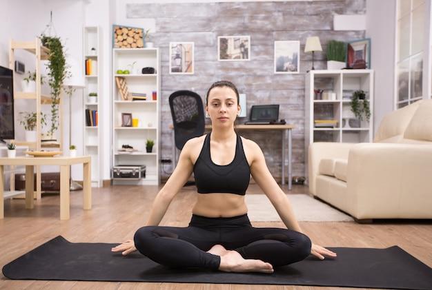 Jonge vrouw die de ogen open houdt terwijl ze op de mat zit in de woonkamer die yoga doet.
