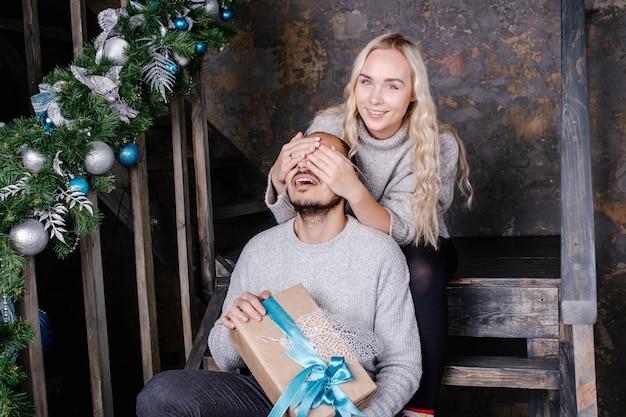 Jonge vrouw die de ogen van de man behandelt met hand en een man verrast met een kerstcadeau.