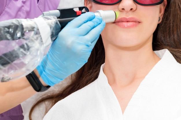 Jonge vrouw die de ontharingsepilation van het laserhaar op gezicht in salon ontvangen