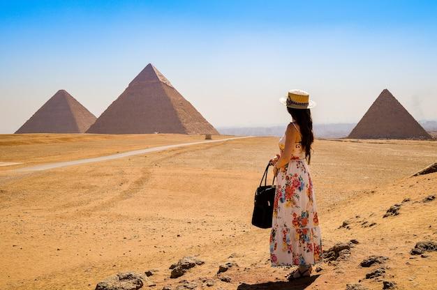 Jonge vrouw die de piramides in egypte bezoekt