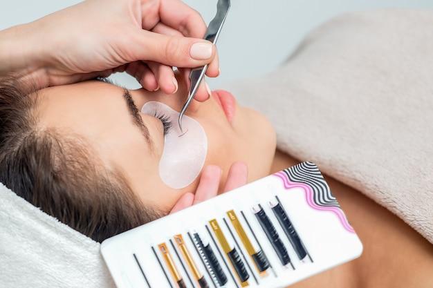 Jonge vrouw die de procedure van de wimperuitbreiding in schoonheidssalon ontvangt.