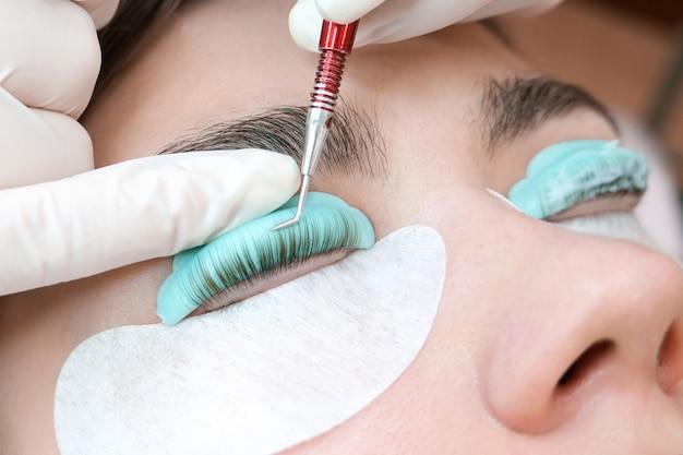 Jonge vrouw die de procedure van het wimperlamineren in een schoonheidssalon doet, close-up