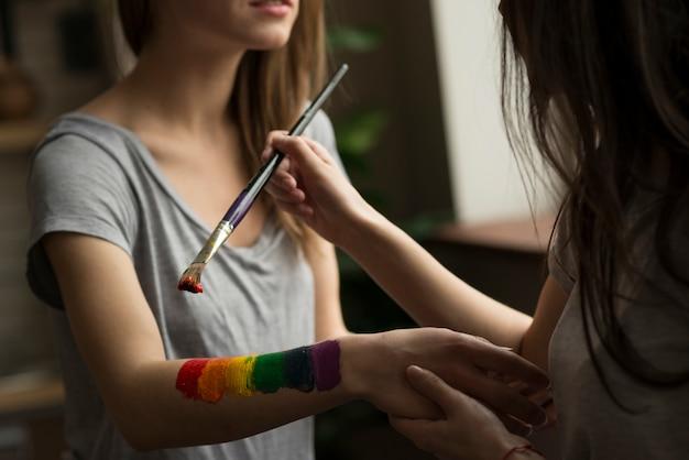 Jonge vrouw die de regenboogvlag over de hand van haar meisje schildert