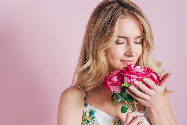 Jonge vrouw die de rozen ruikt tegen roze achtergrond