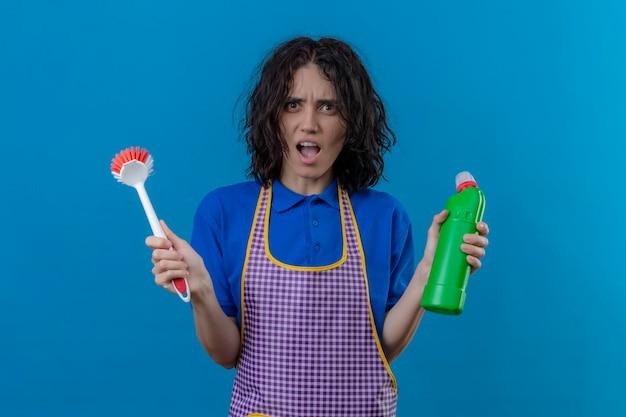 Jonge vrouw die de schrobborstel van de schortholding en een fles schoonmakende leveringen draagt geschokt met wijd open mond die zich over blauwe achtergrond bevindt