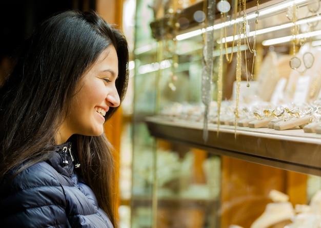 Jonge vrouw die de showcase van openlucht juwelen bekijkt
