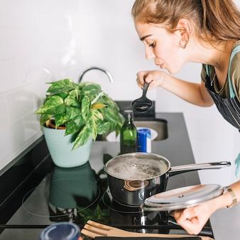 Jonge vrouw die de soep in de keuken proeft