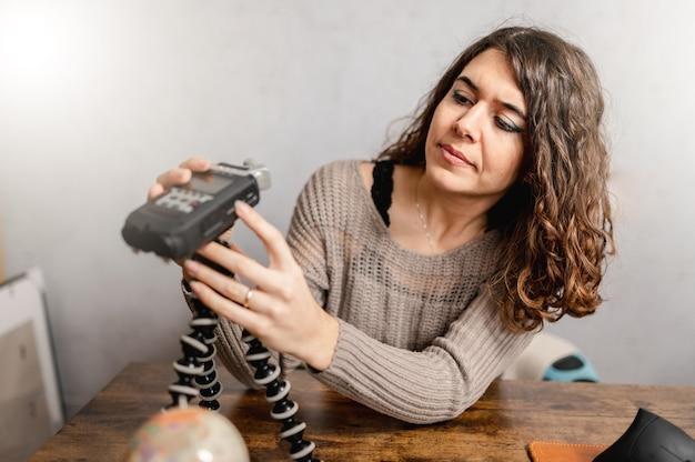 Jonge vrouw die de spreker van de voicerecorder opzetten die op een statief wordt geplaatst.