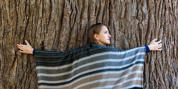 Jonge vrouw die de stam van een grote boom koestert. eenheid met de natuur, herfst bos