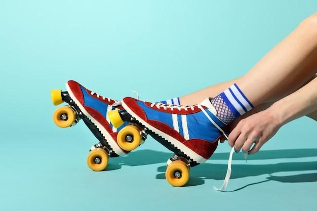 Jonge vrouw die de veters op haar rode en blauwe rolschaatsen bindt