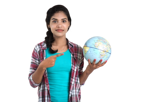 Jonge vrouw die de wereldbol houdt en op een witte muur stelt.