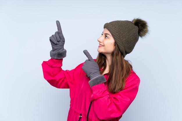 Jonge vrouw die de winterkleren over geïsoleerde muur draagt