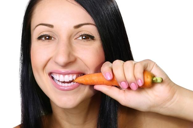 Jonge vrouw die de wortel eet, over wit