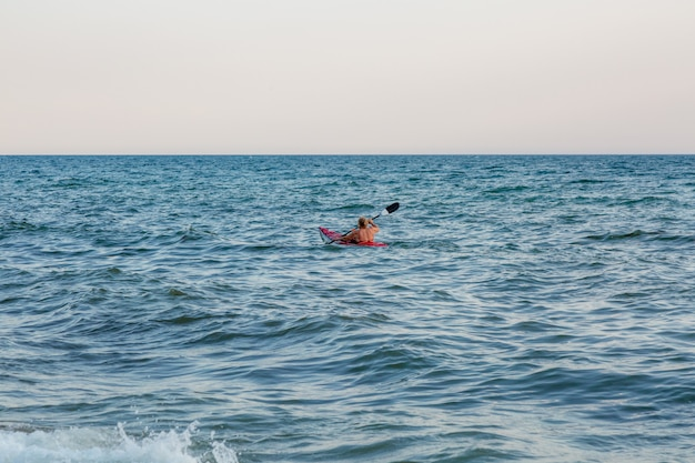 Jonge vrouw die de zeekajak paddelt. actieve vakantie.