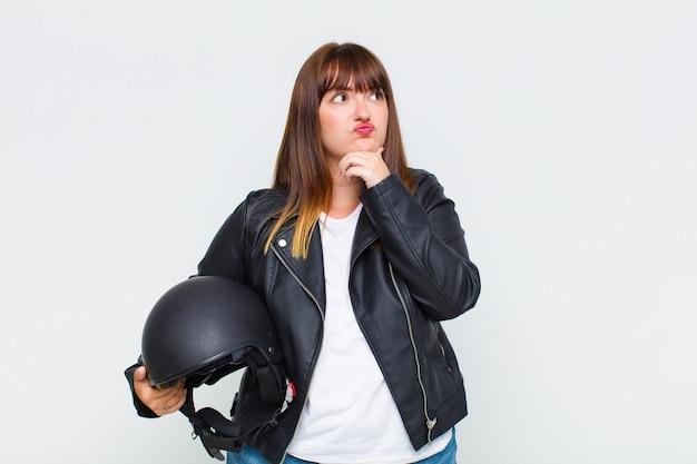 Jonge vrouw die denkt, zich twijfelachtig en verward voelt, met verschillende opties, zich afvraagt welke beslissing ze moet nemen