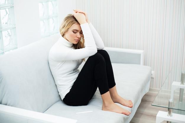 Jonge vrouw die depressief en droevig voelen na thuis het bekijken het resultaat van de zwangerschapstest