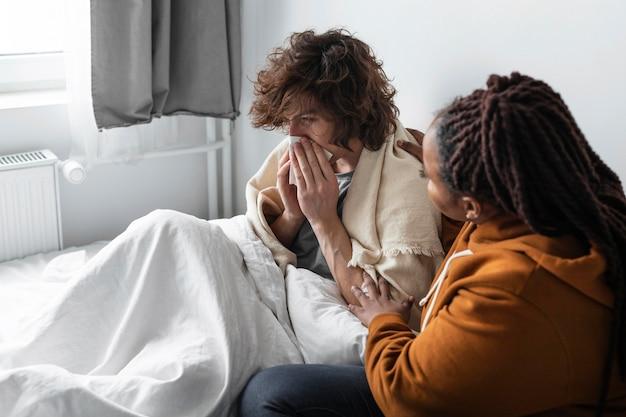 Jonge vrouw die dicht bij haar zieke vriend is