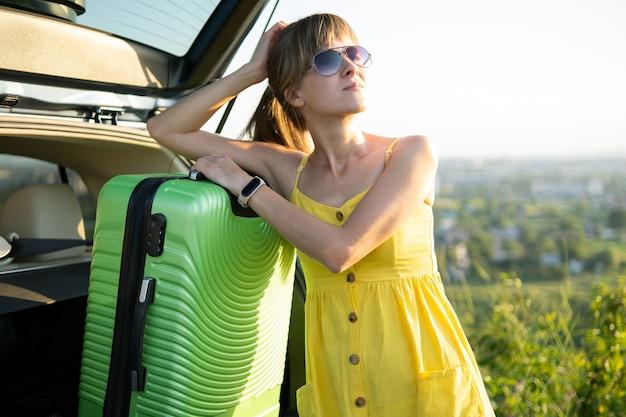 Jonge vrouw die dichtbij haar auto rust die op een groene koffer in de zomeraard leunt