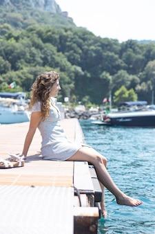 Jonge vrouw die dichtbij het overzees ontspant