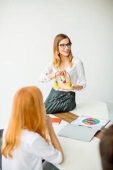 Jonge vrouw die didactisch speelgoed voorstelt