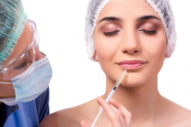Jonge vrouw die die voor plastische chirurgie voorbereidingen treft op wit wordt geïsoleerd